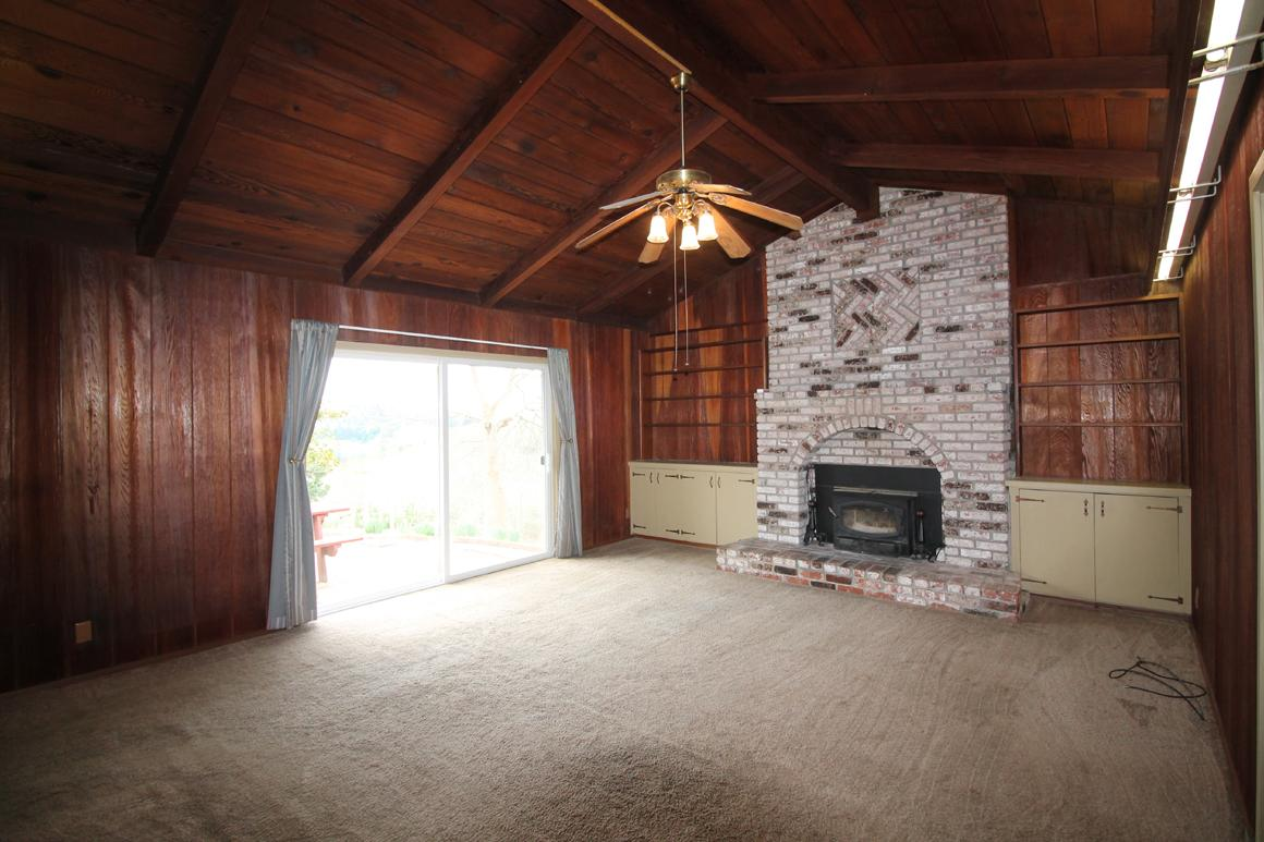 Living room with vaulted ceiling and brick surround fireplace