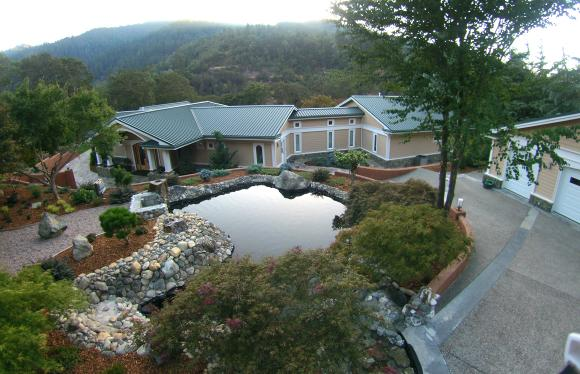 Beautiful home showing front pond landscaping